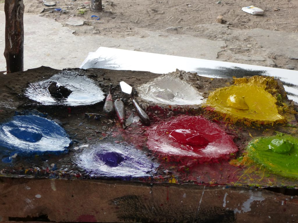 Palette with blue, purple, red, green, yellow, white, and black paint spots and three small spatulas