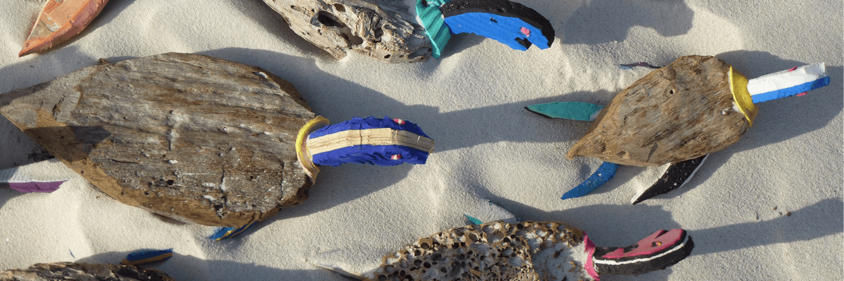 Colorful wooden turtles covered by the sun on the white sand