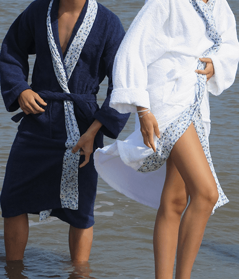 Man and woman with their feet covered by the water and wearing sustainable dark blue and white bathrobes