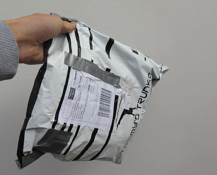Hand holding a white and black striped Tommy's Trunks bag with a shipment label