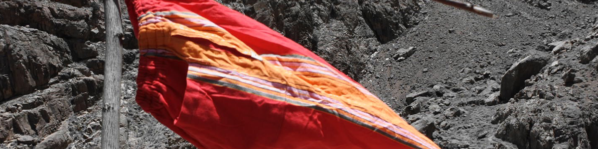 Eco-friendly red and orange kikoy pants hanging from a branch and with dirt and rocks as background