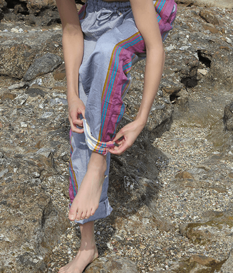 Barefoot woman standing on rocks and rolling up her sustainable gray and purple kikoy pants