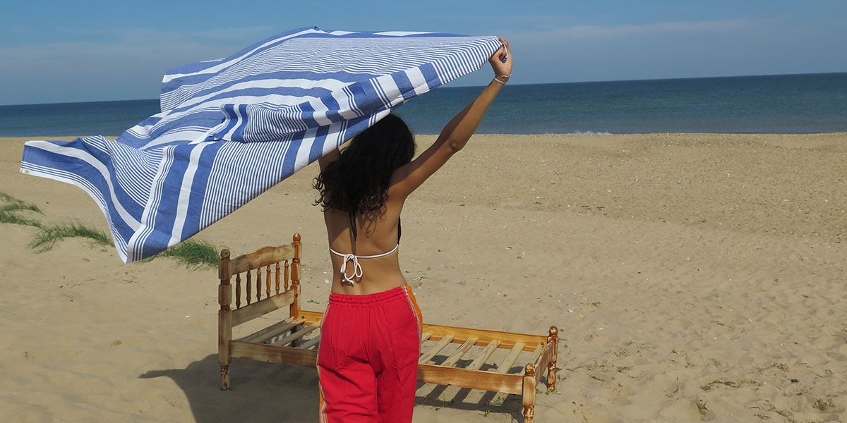Brunette girl on the beach wearing red kikoy pants and holding a striped blue kikoy towel over her head