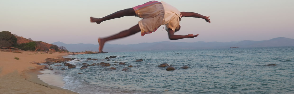 Man wearing sustainable gray and purple kikoy shorts doing a backflip on the beach