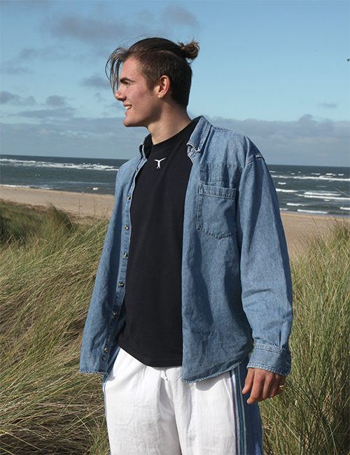 Smiling man standing on the beach wearing a denim shirt, black t-shirt and white and blue kikoy pants