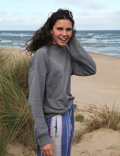 Brunette smiling girl standing in the beach and wearing a gray sweatshirt and colorful striped kikoy pants