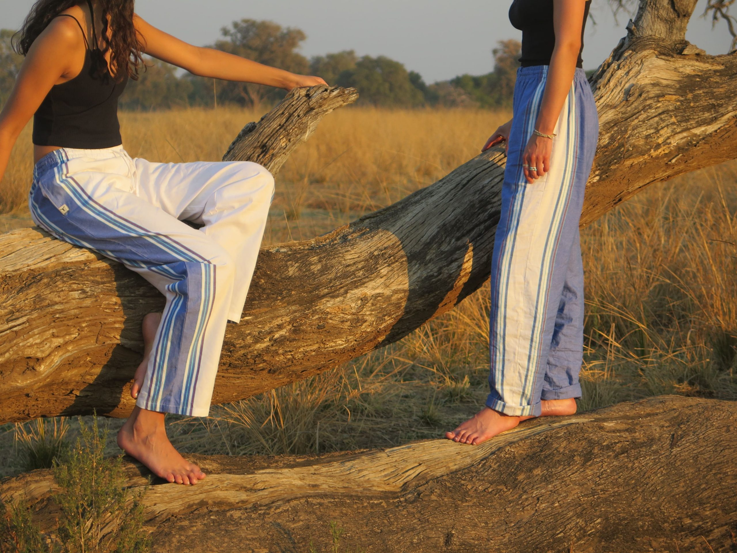 Two barefoot girls sitting and standing on a fallen log wearing sustainable blue and white kikoy pants