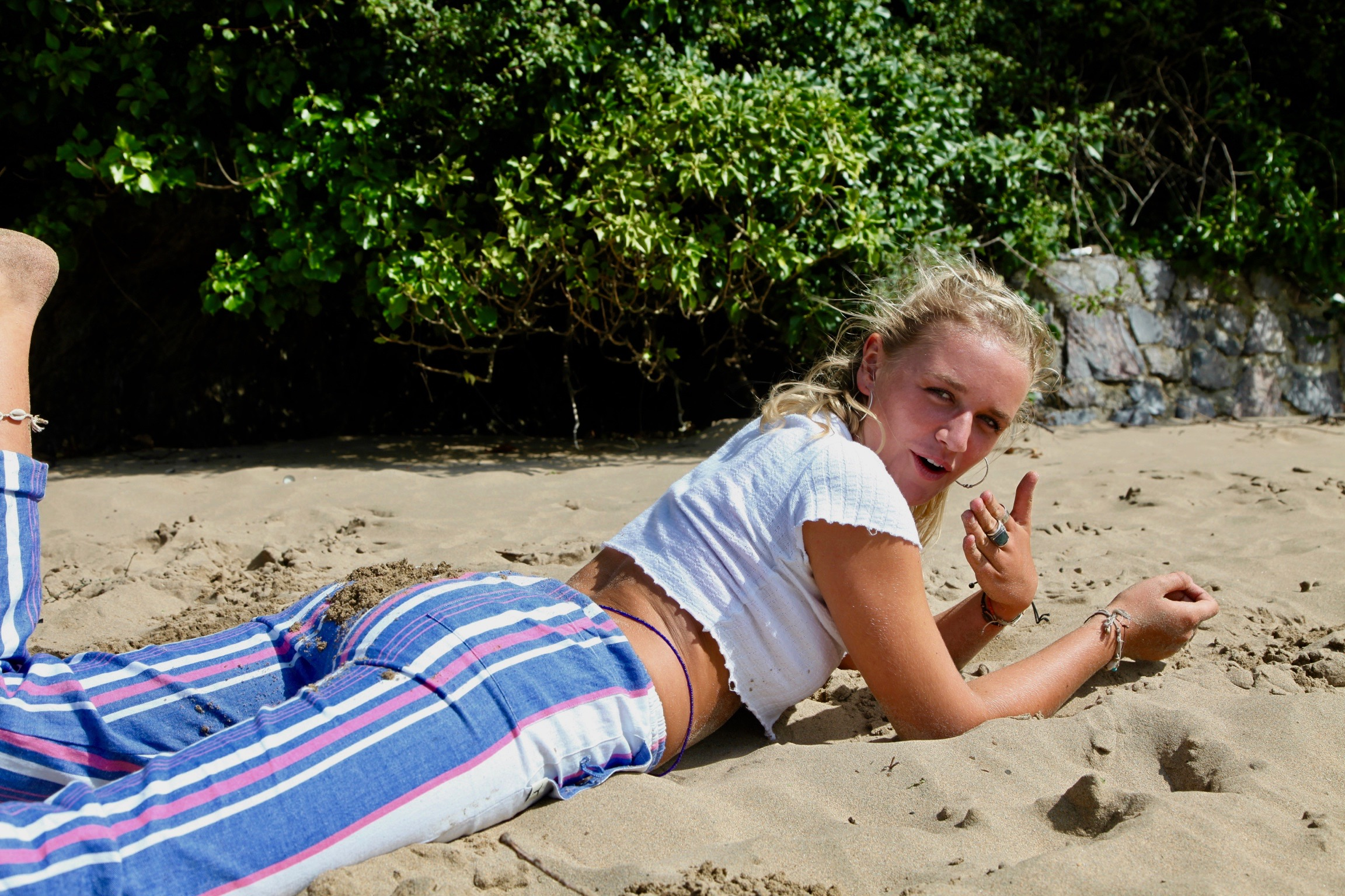 Blonde woman laying face down on the sand faking anguish and wearing colorful striped kikoy pants