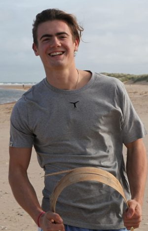 Smiling young man standing on the beach wearing a sustainable gray t-shirt with the sea behind him
