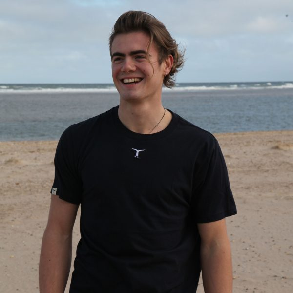Smiling young man standing on the beach wearing a sustainable black t-shirt with the sea behind him