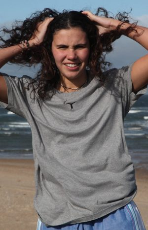 Smiling woman standing on the beach with her hands on her head wearing a gray t-shirt and kikoy yoga pants