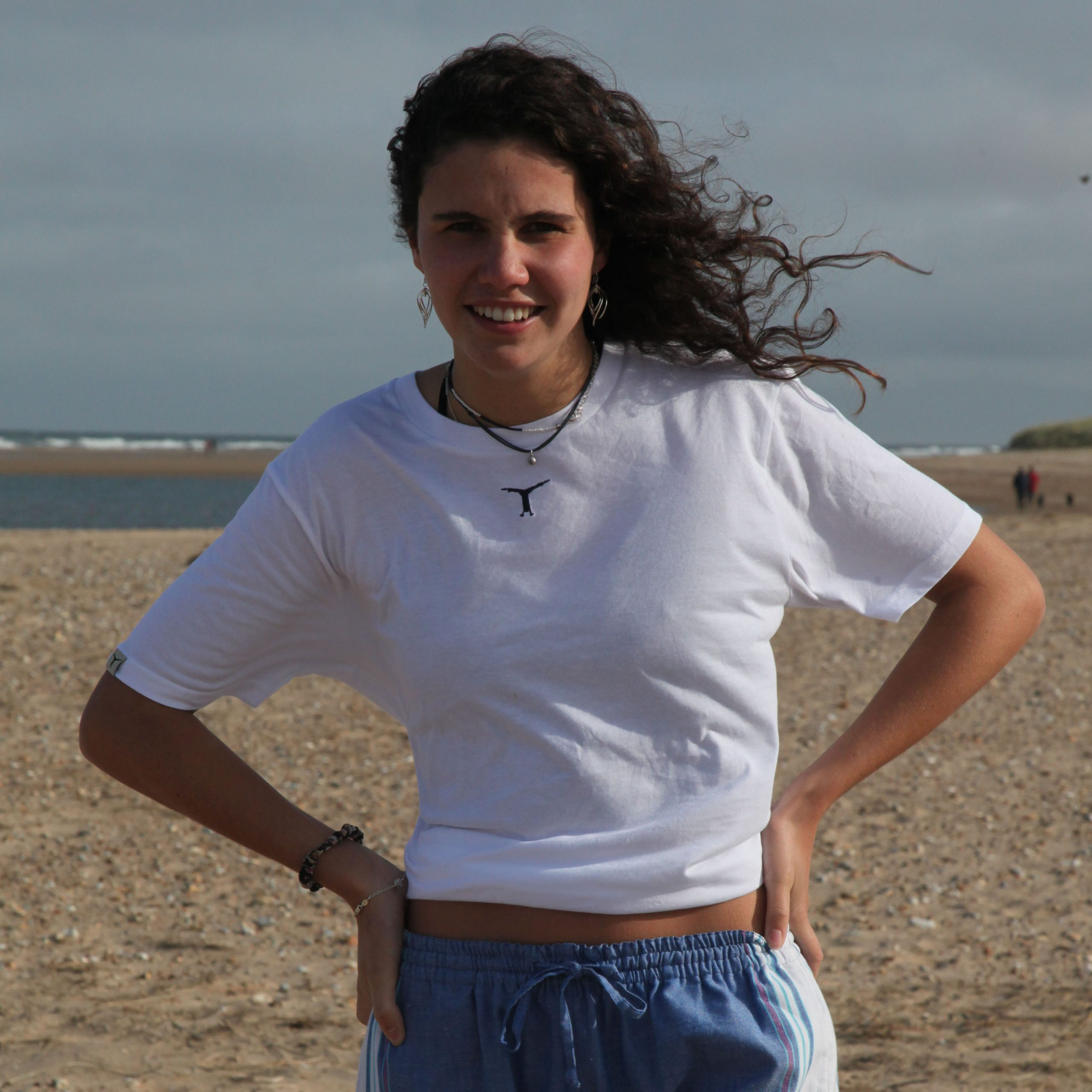 Smiling woman standing on the beach with her hands on her hips wearing a white t-shirt and kikoy yoga pants