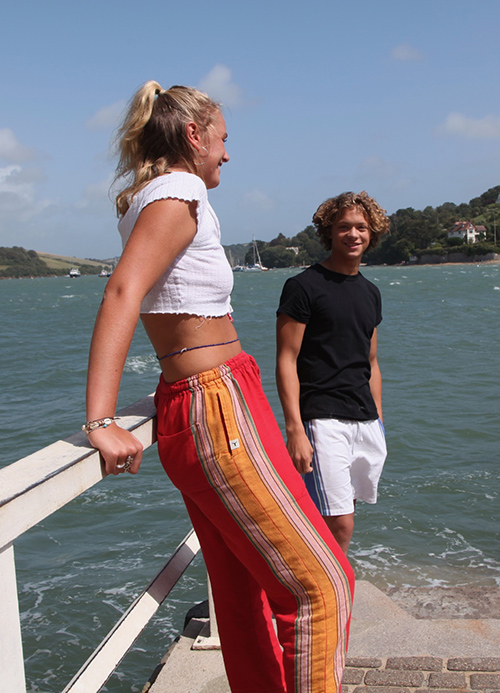 Blond girl and blonde boy relaxing near the sea and wearing eco-friendly colorful kikoy pants and shorts