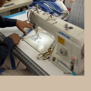 Man sewing a blue kikoy line for eco-friendly clothing on a white sewing machine