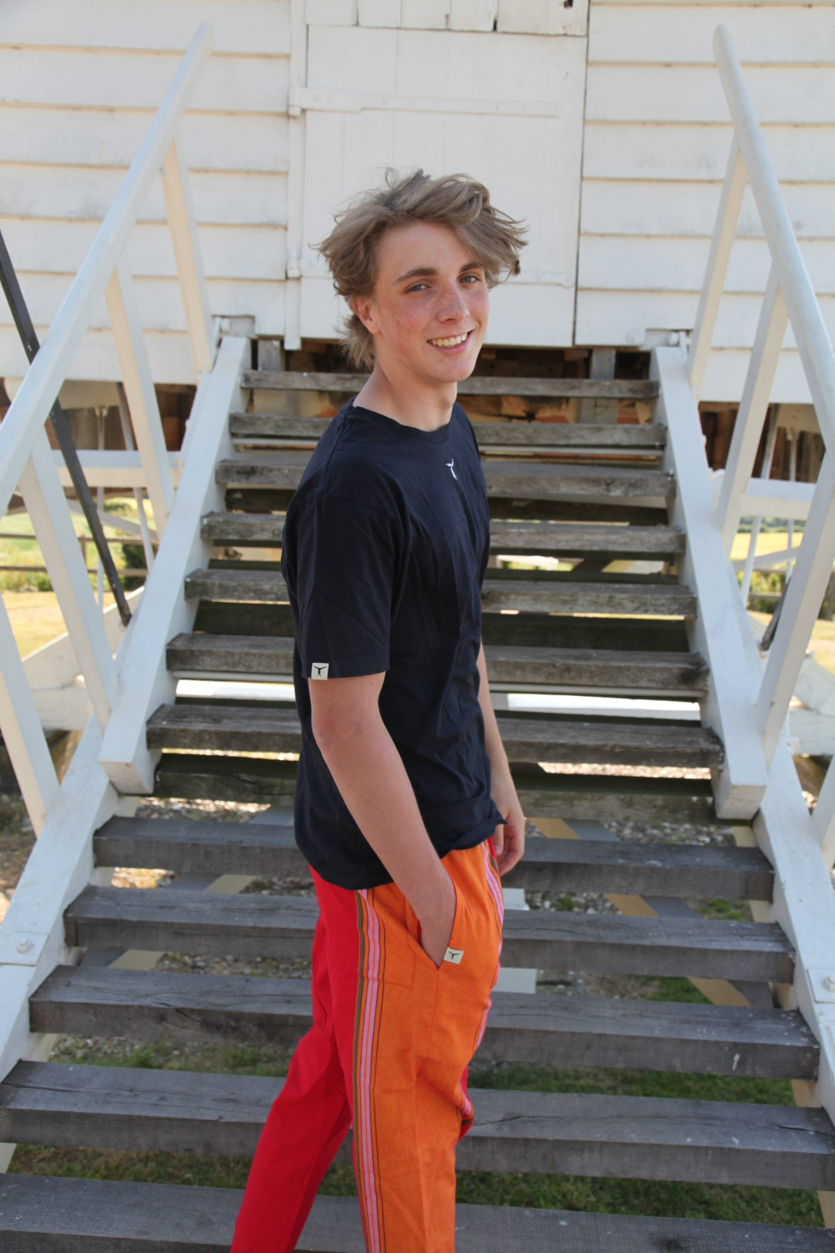Smiling young man standing in profile on wooden stairs wearing a black t-shirt and colorful kikoy yoga pants