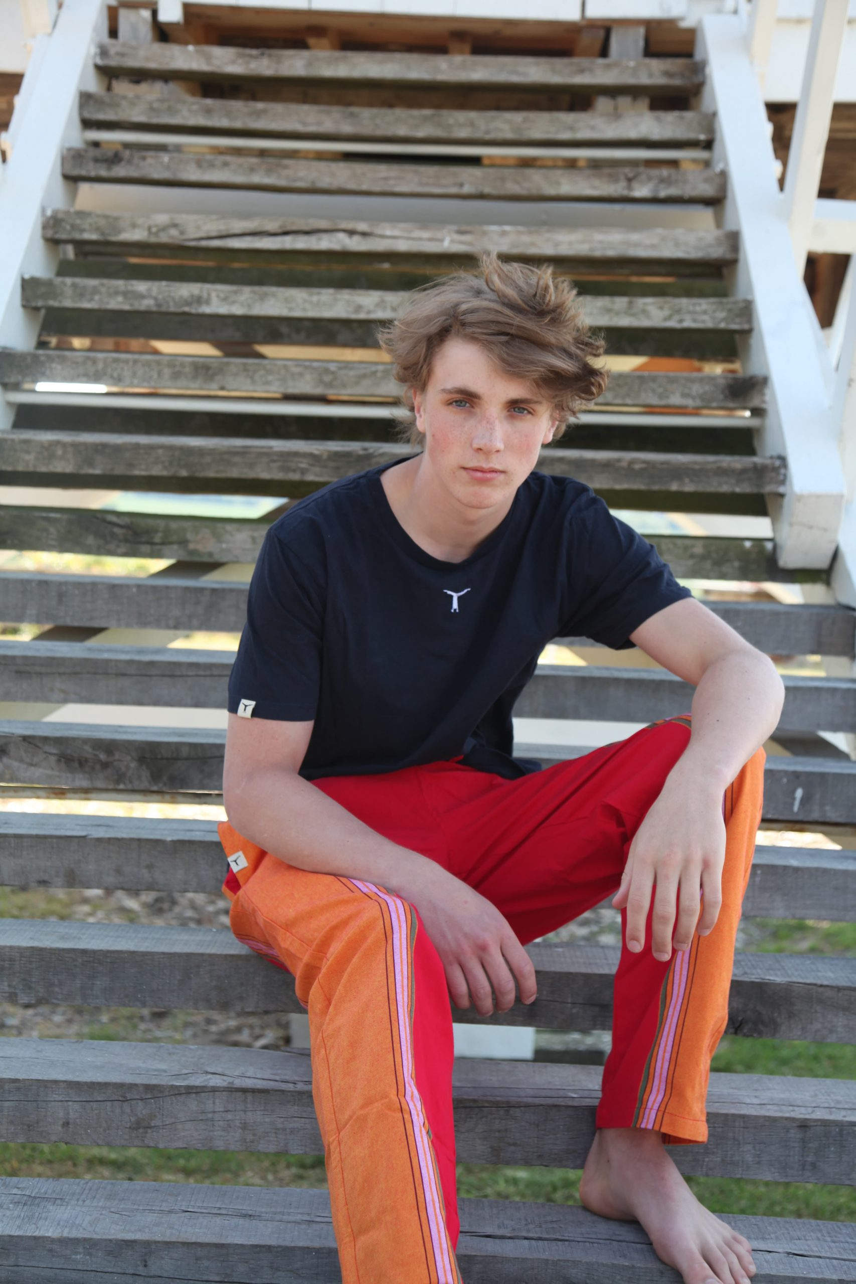 Young man sitting on outdoor wooden stairs wearing a black t-shirt and red and orange kikoy yoga pants