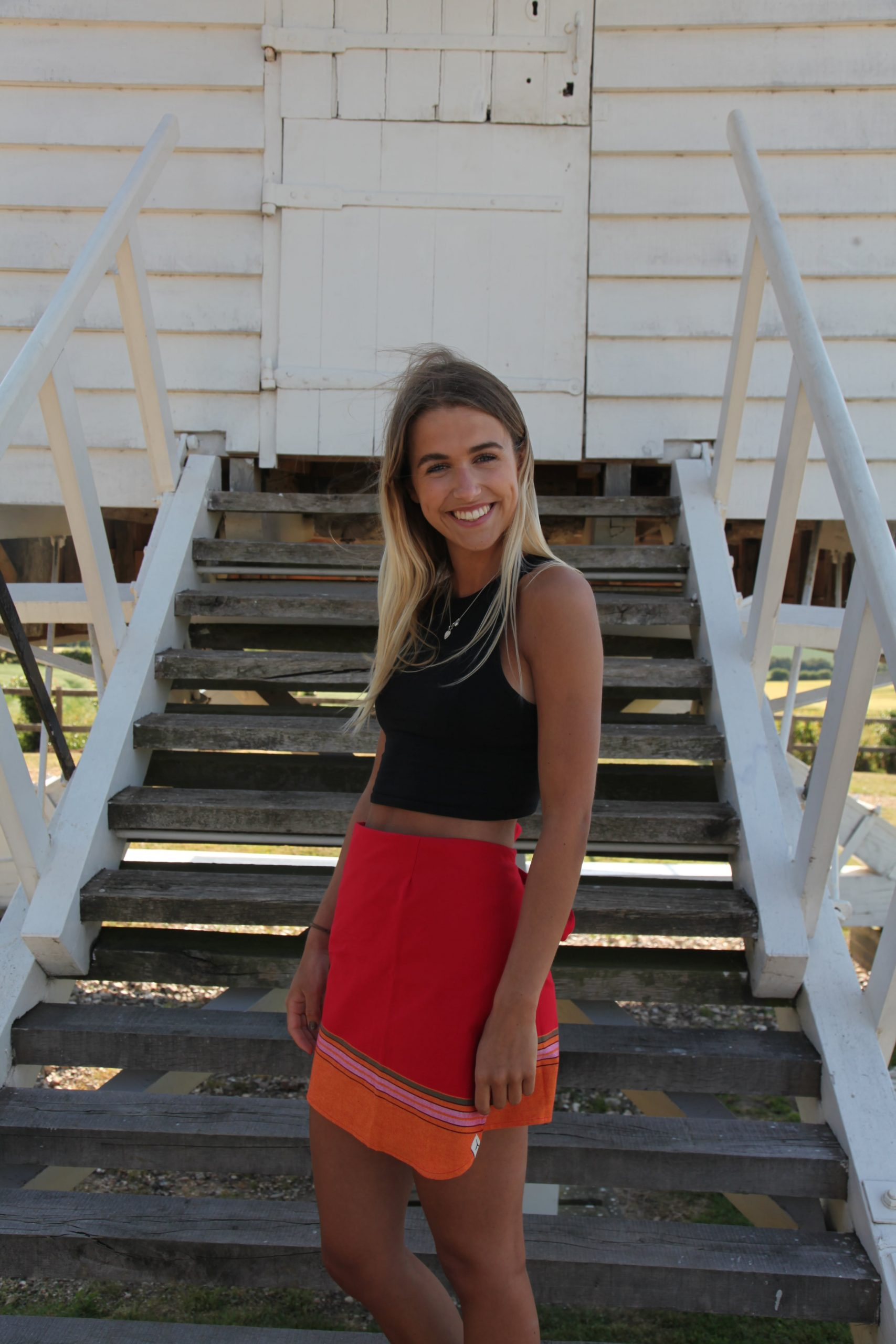 Smiling girl standing on outdoor wooden stairs wearing a black top and a colorful red and orange kikoy skirt