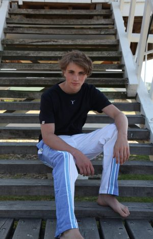 Young man sitting on outdoor wooden stairs wearing a black t-shirt and blue and white kikoy yoga pants