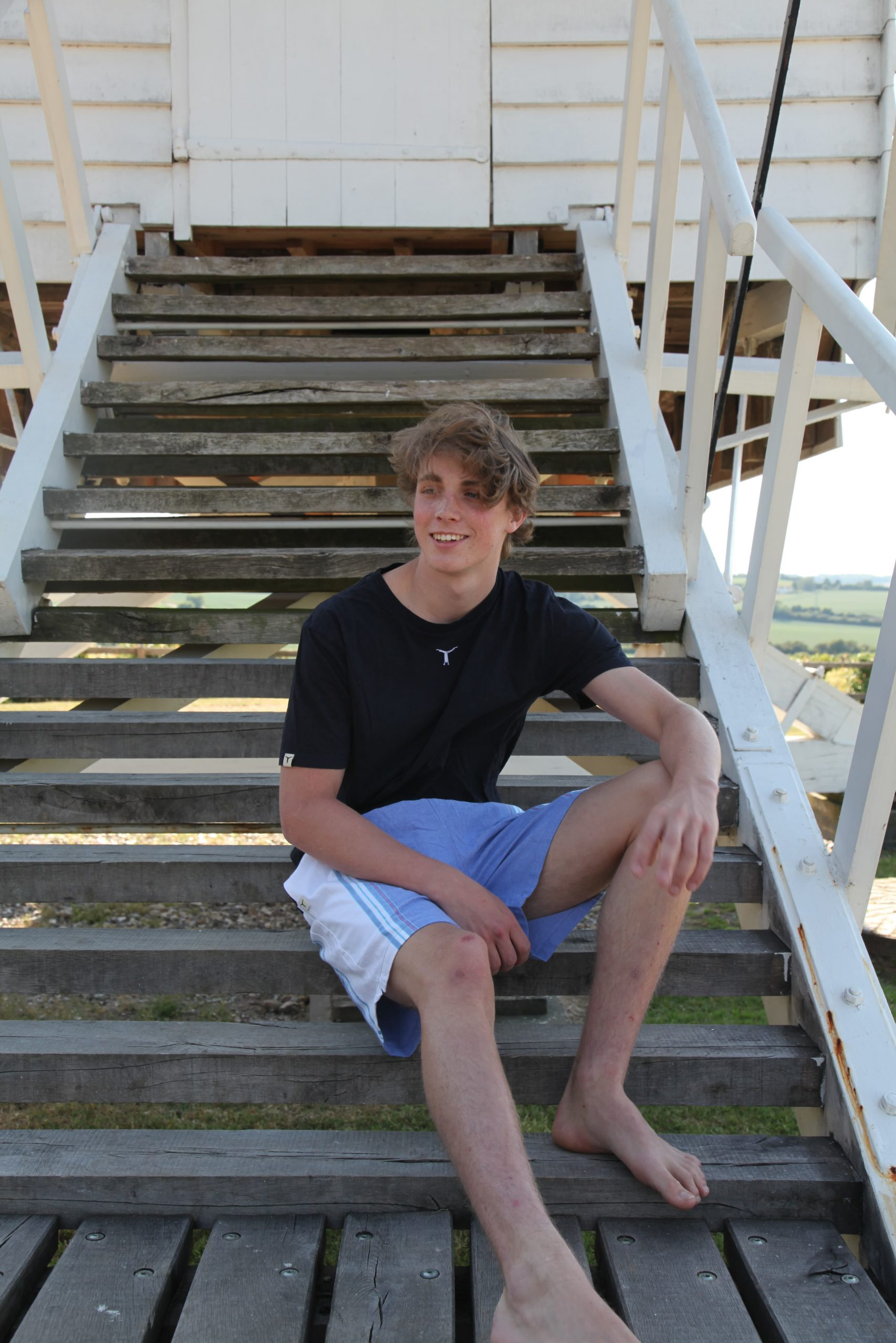 Smiling young man sitting on outdoor wooden stairs wearing a black t-shirt and eco-friendly colorful kikoy shorts