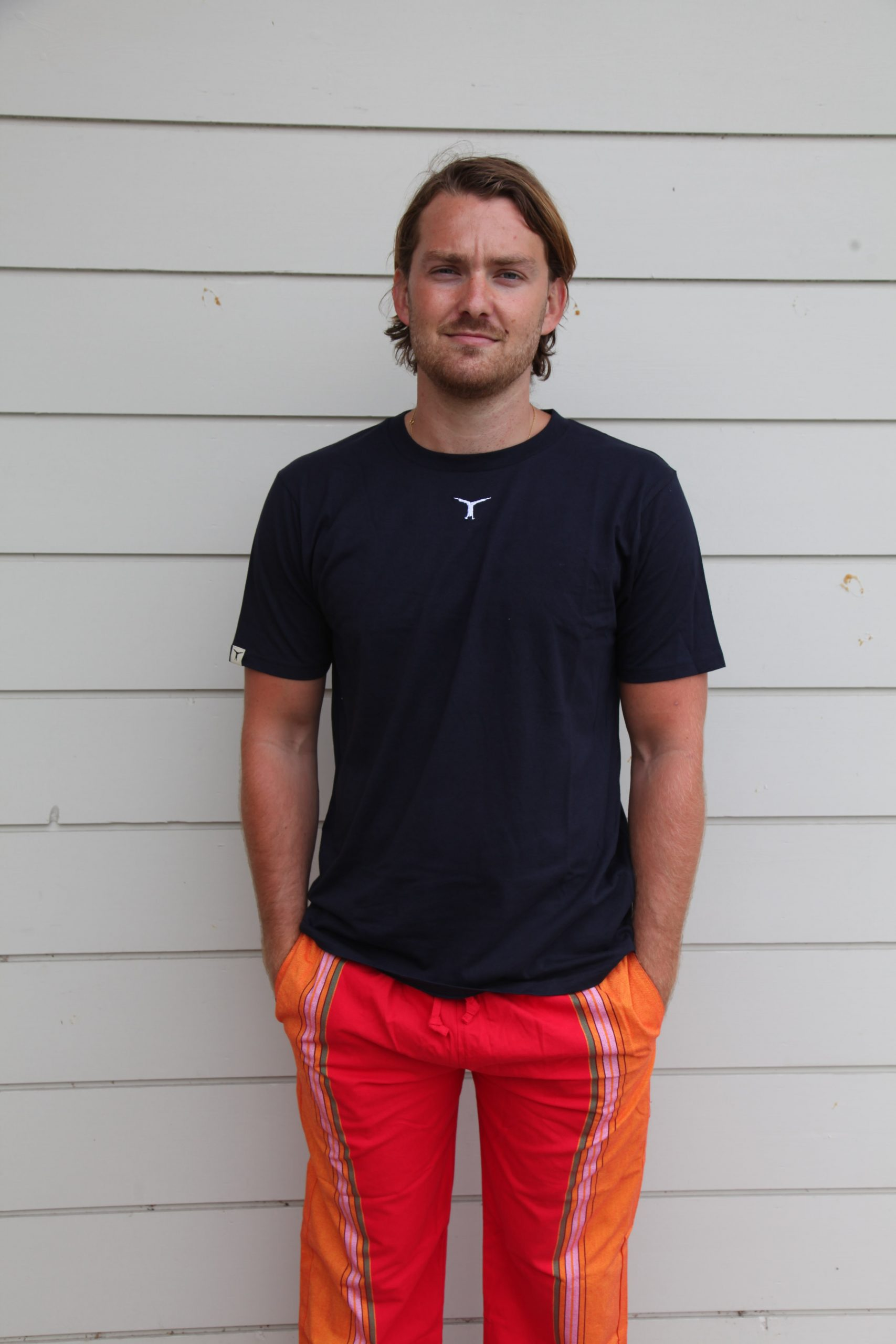 Man standing in front of a wall wearing a black t-shirt and sustainable red and orange kikoy pants