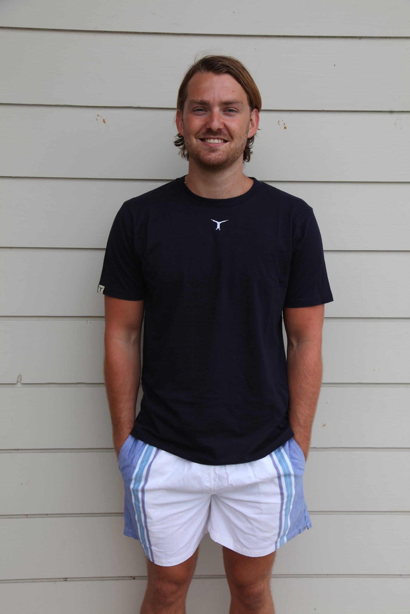 Smiling man standing in front of a wall wearing an eco-friendly t-shirt and white and blue kikoy shorts
