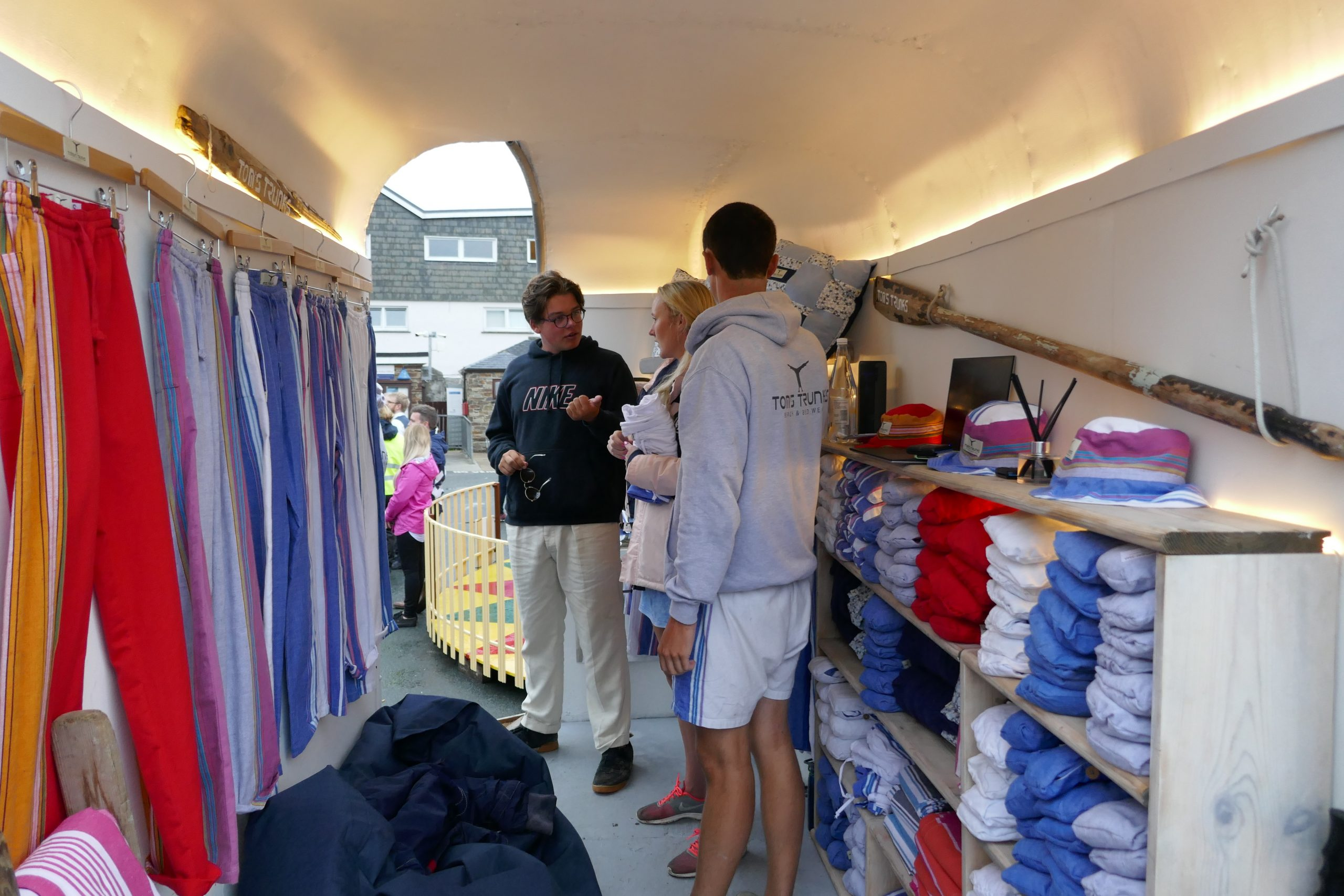 Two men and a woman inside a trailer full of colorful kikoy yoga pants and eco-friendly hats and clothing