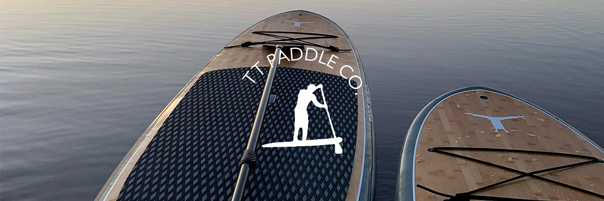 Brown and black paddleboards floating on the water and with the TT logo on them