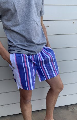Man standing in front of a wall with his hands in his pockets and wearing sustainable and colorful kikoy shorts